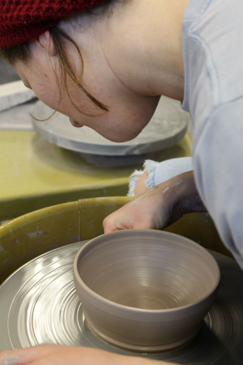 Student forming bowl on pottery wheel
