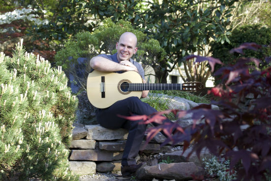 Isaac Lausell with guitar in Faner garden